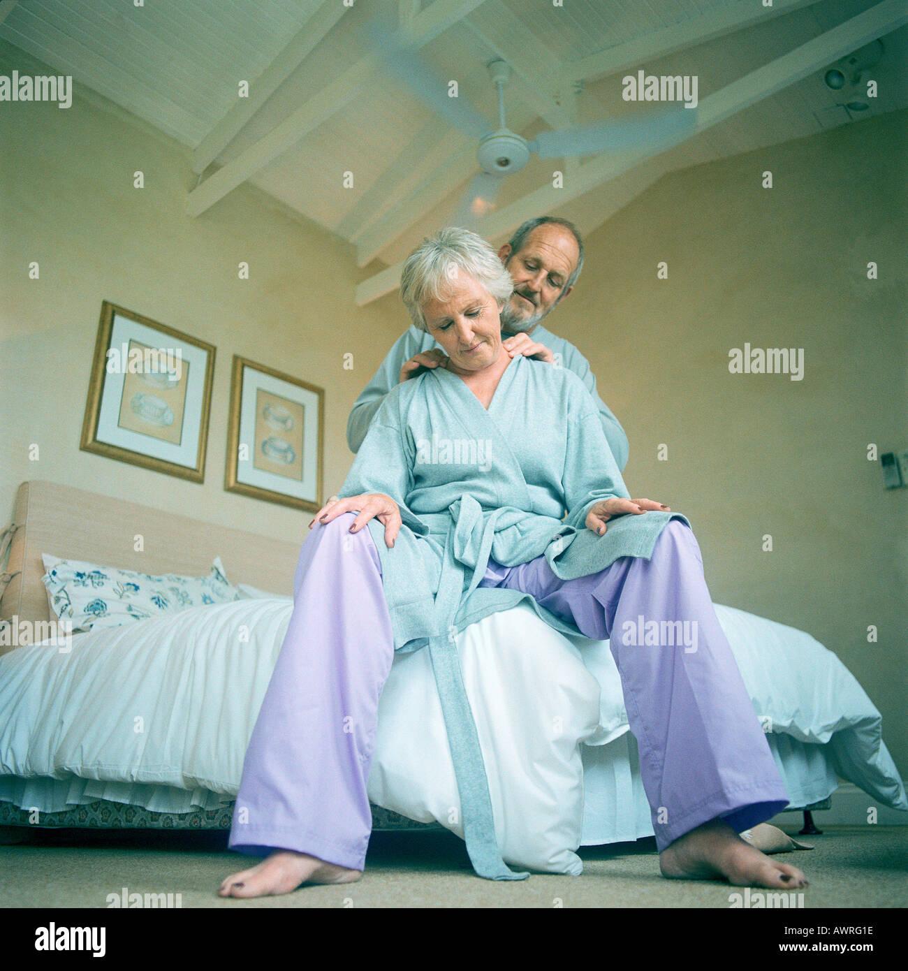 Mature man massaging woman, low angle view Stock Photo