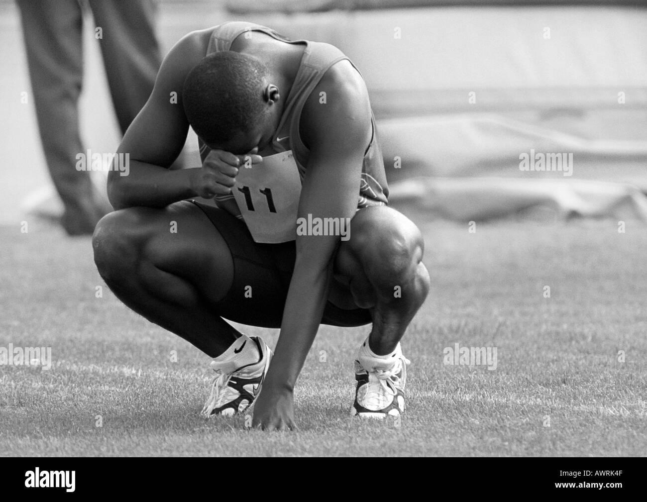 Male athlete crouching, head down, b&w - Stock Image