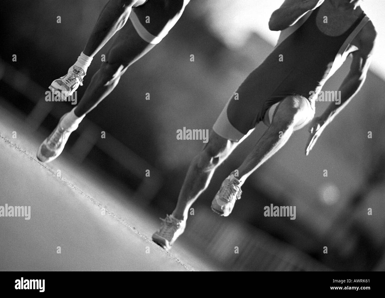 Male athletes running, close-up, b&w Stock Photo