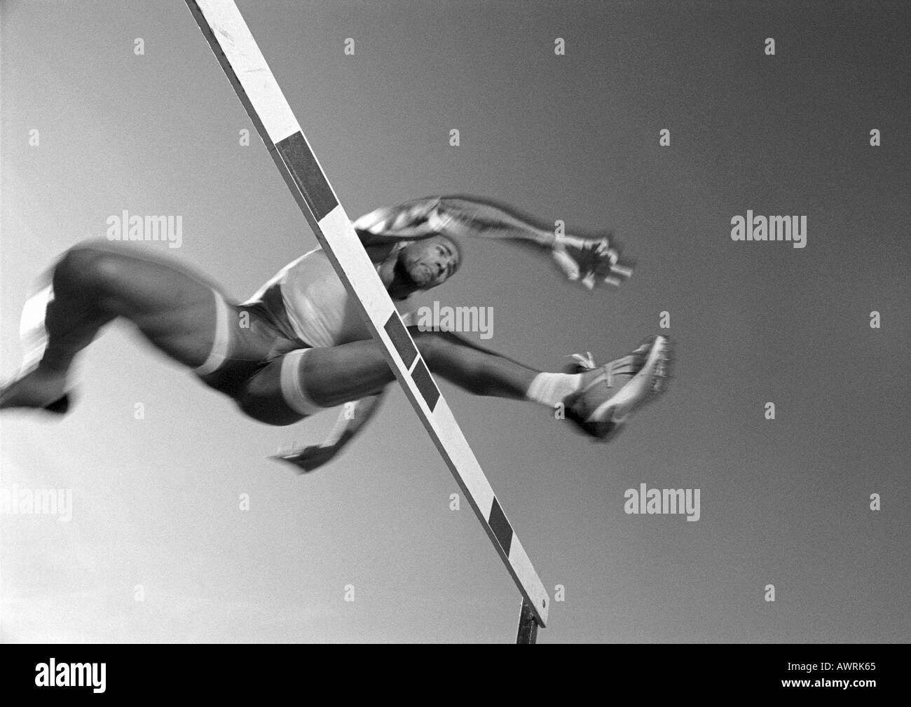 Male athlete jumping hurdle, low angle view, blurred motion, b&w - Stock Image