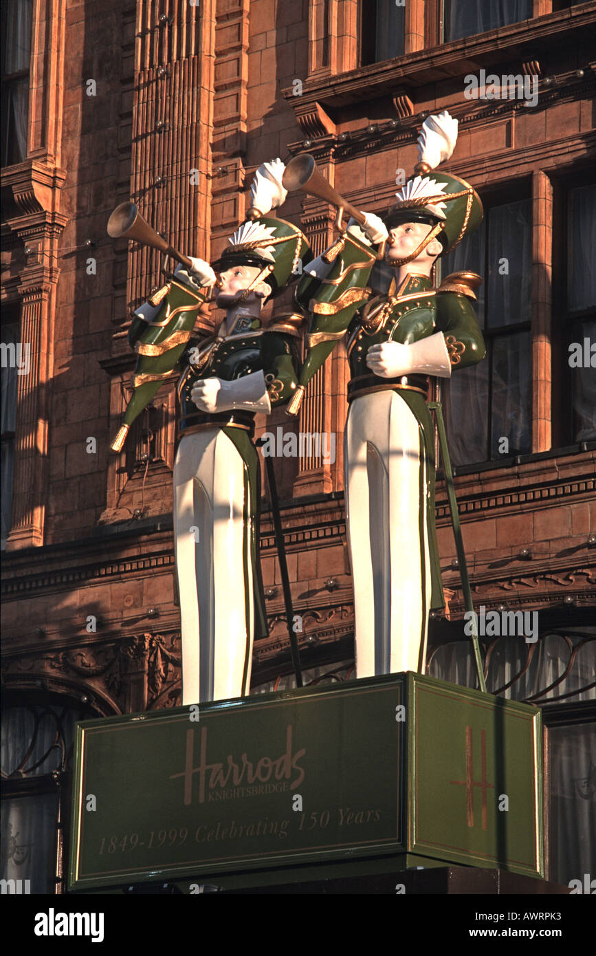 Trumpet blowing statues mounted above an entranceway to Harrods department store Knightsbridge London England - Stock Image