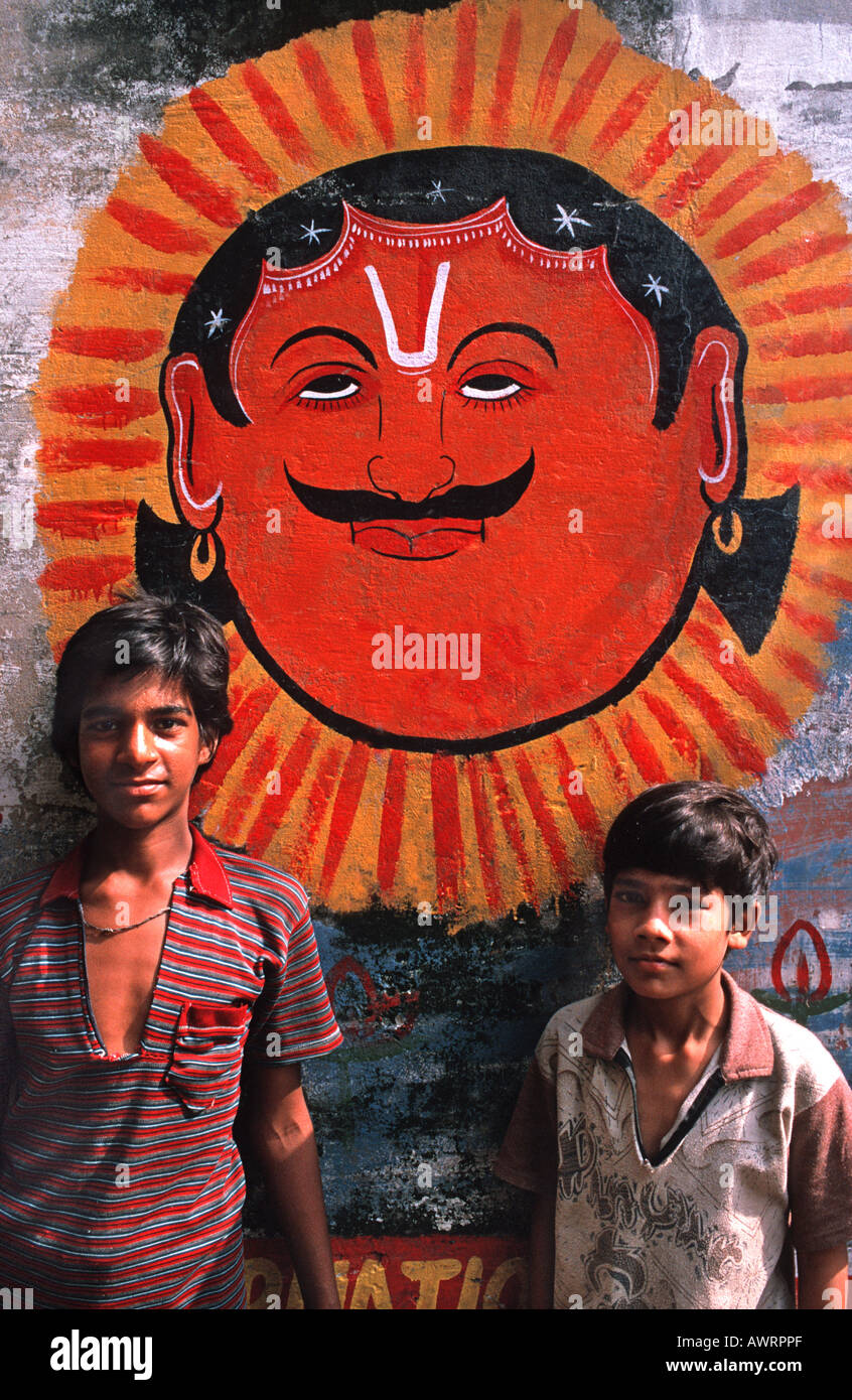 Indian boys standing in front of a colourfully painted wall Delhi India - Stock Image