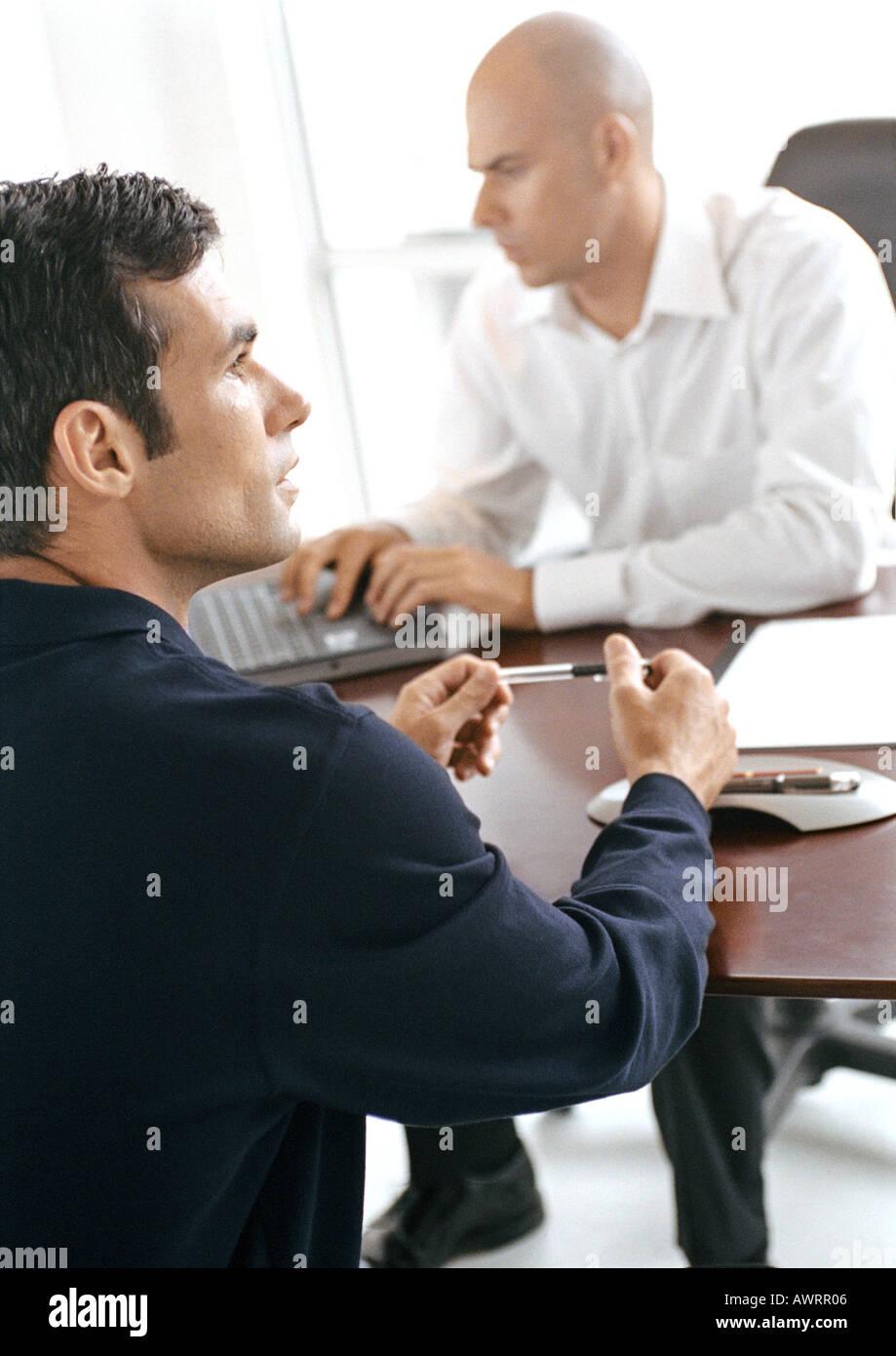 Businessmen sitting at desk - Stock Image