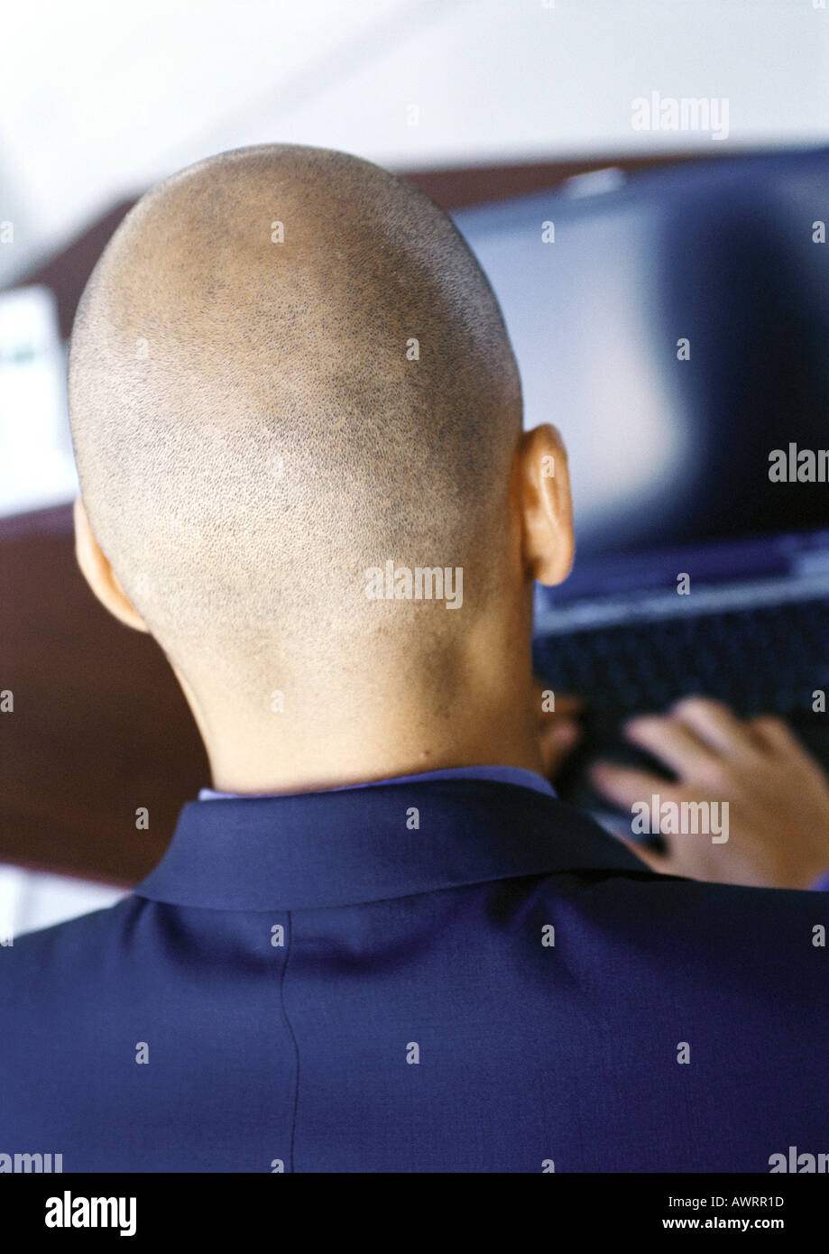 Man working on computer, rear view, close-up - Stock Image