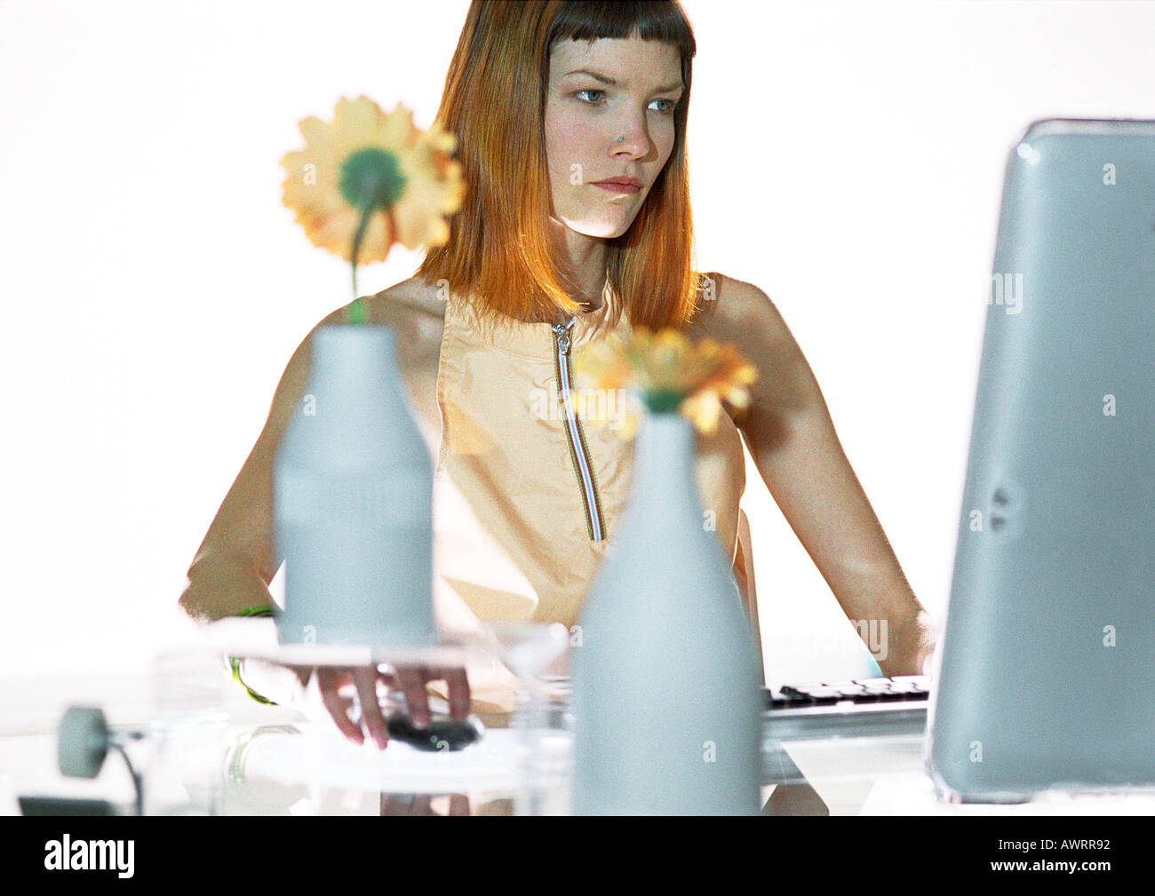 Woman using flat screen computer at desk - Stock Image