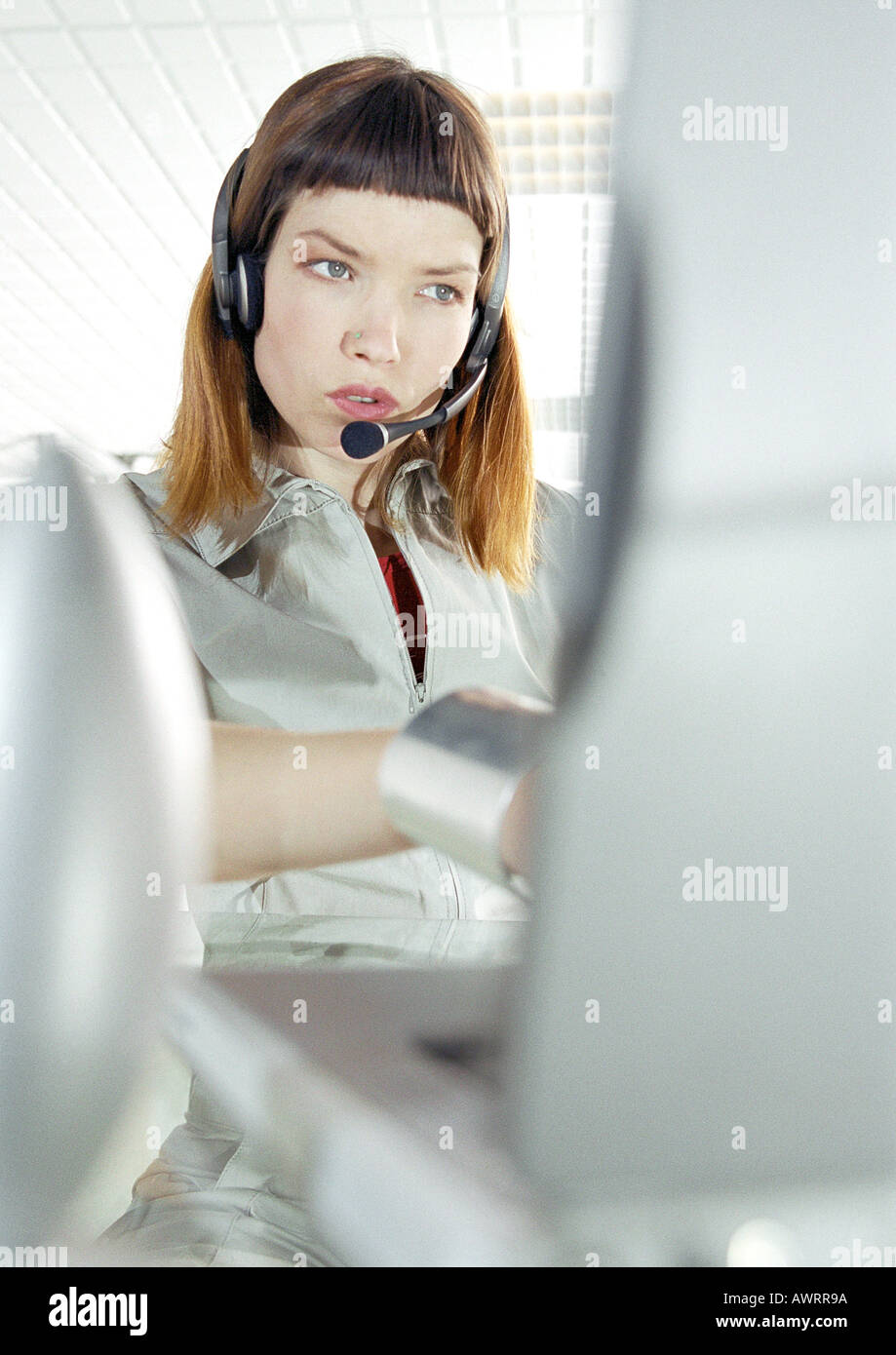 Woman at desk wearing headset - Stock Image