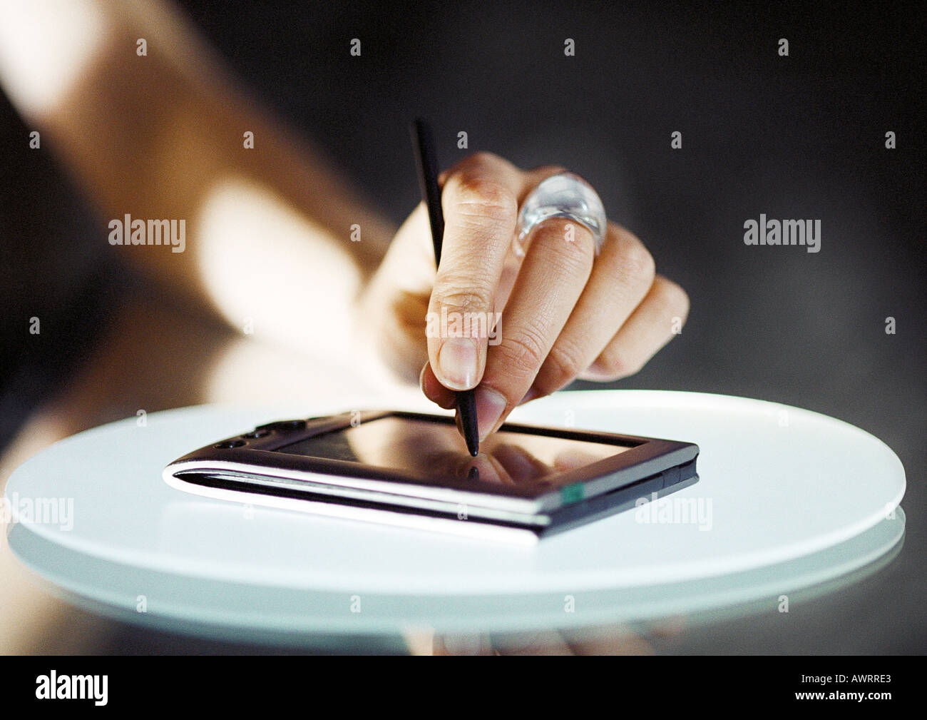 Hand using pocket computer, close-up - Stock Image