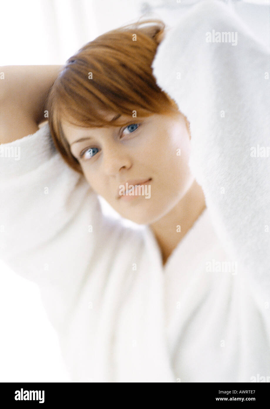 Woman with hands behind head, portrait, close-up - Stock Image