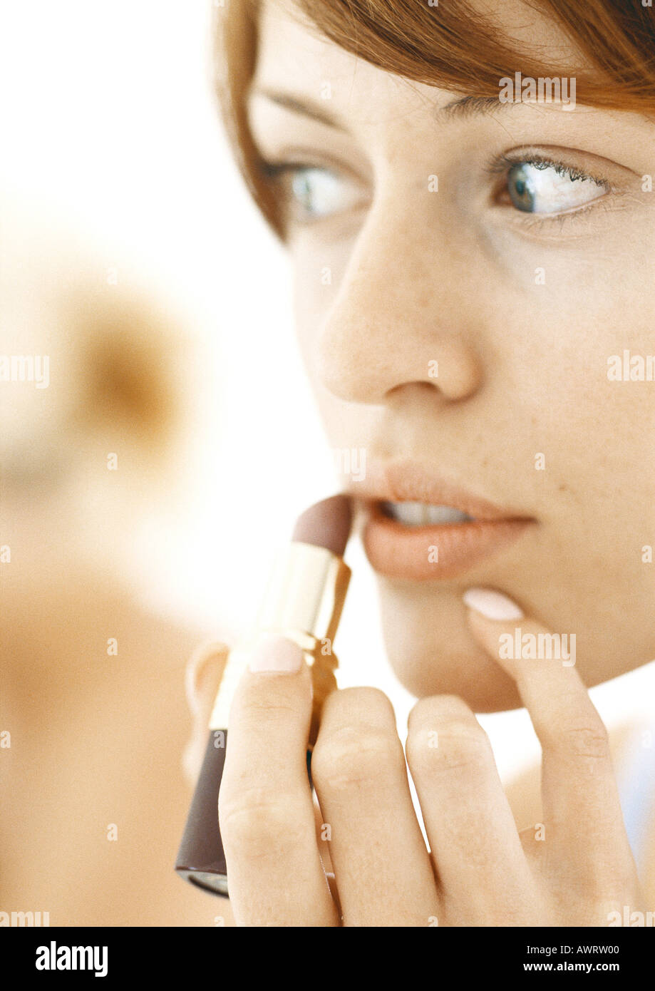Woman using lipstick, close-up - Stock Image