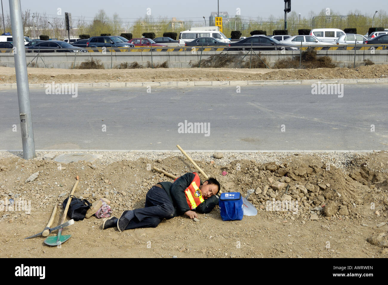 A worker lying on ground while planting trees in the 2008 Olympic Park in Beijing, China. 14-Mar-2008 - Stock Image