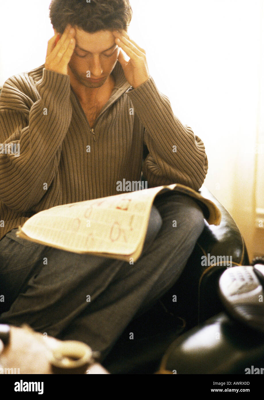 Man rubbing head with newspaper on knees - Stock Image