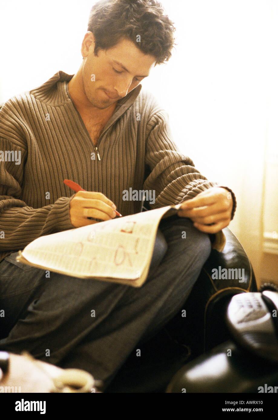 Man writing on newspaper - Stock Image
