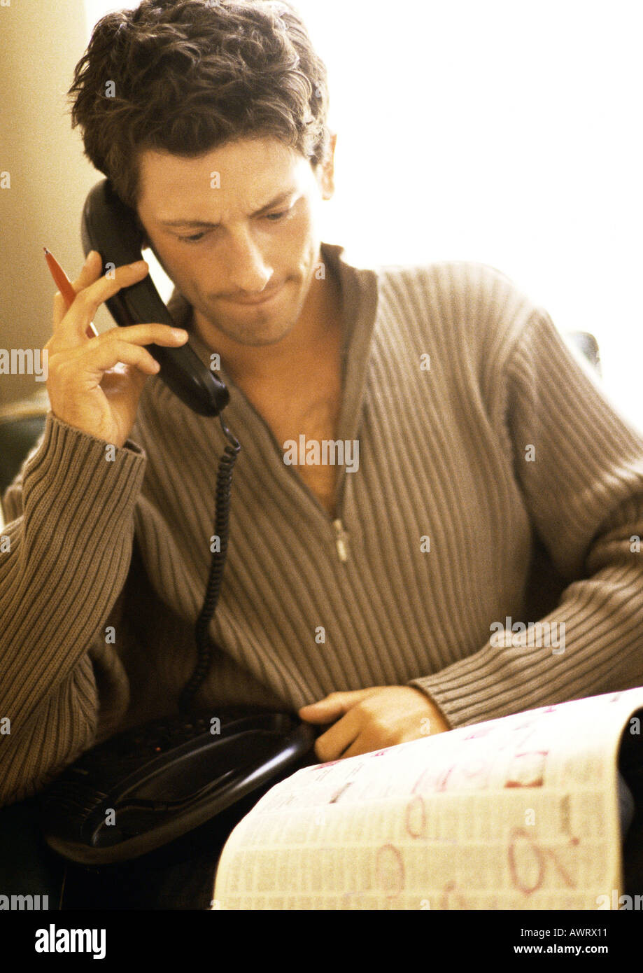 Man phoning with newspaper on knees - Stock Image