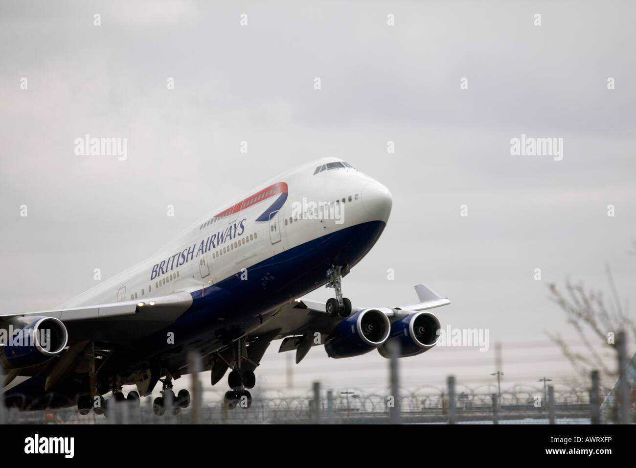 A British Airways Boeing Jumbo Jet takes off at London Heathrow Airport over security fences - Stock Image