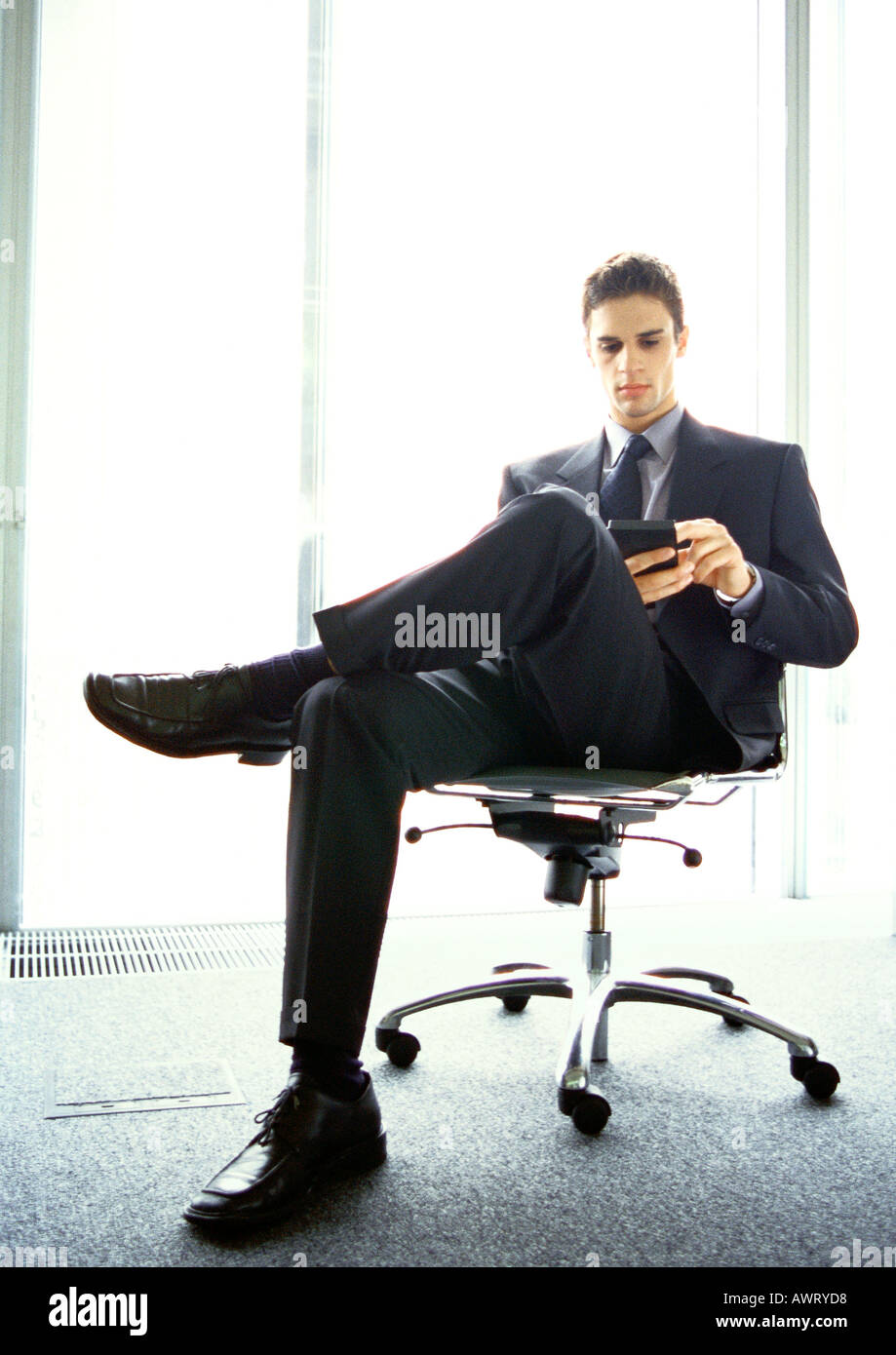 Businessman sitting in chair - Stock Image