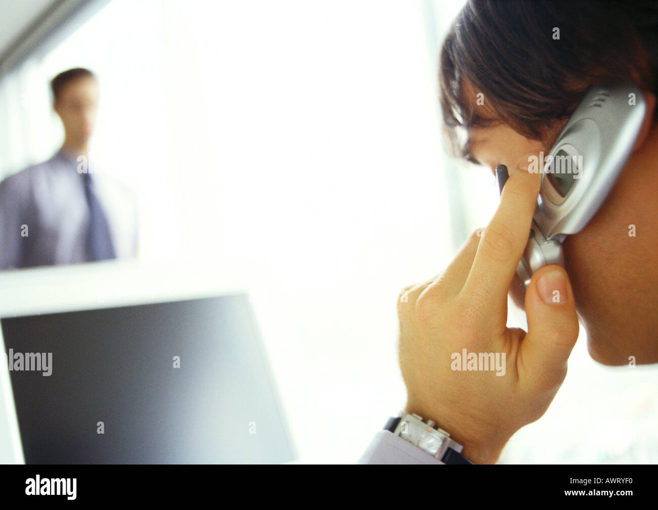 Businessman on cell phone facing computer, side view, close-up - Stock Image