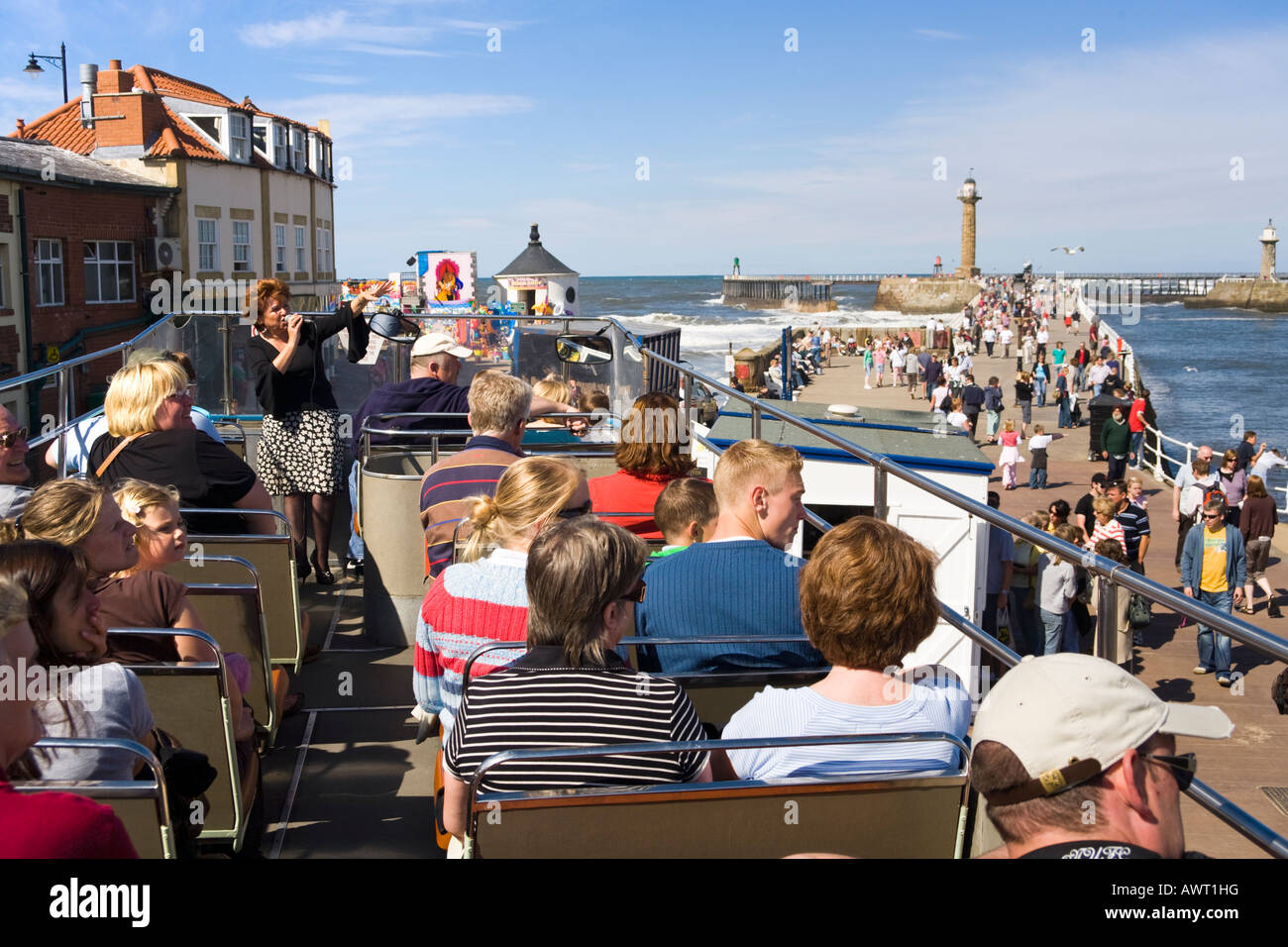 Tourist guide explaining the sights to visitors on an open topped bus beside the harbour at Whitby, North Yorkshire - Stock Image