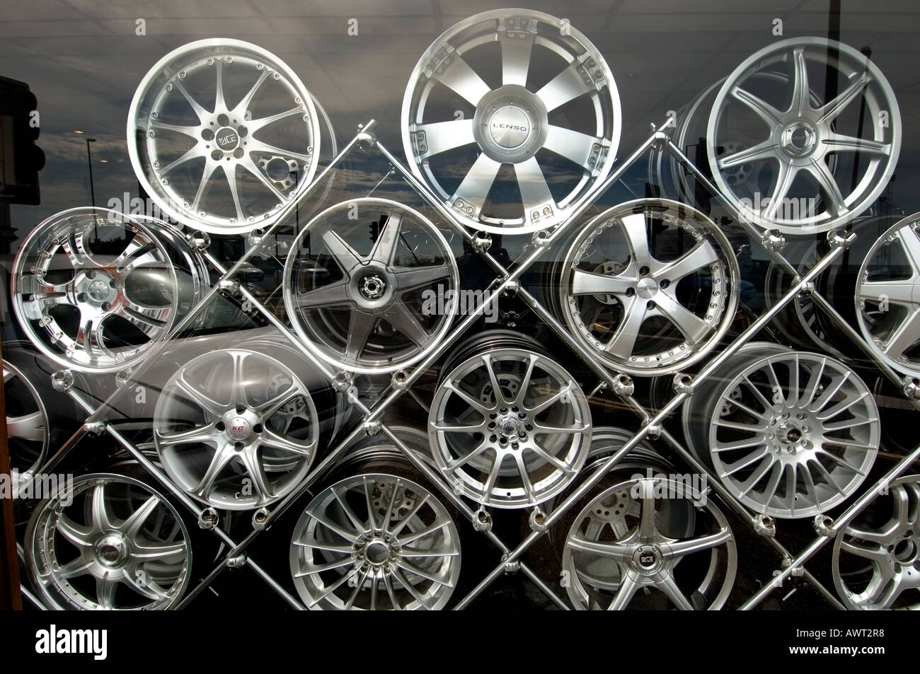 Designer alloy aluminium car wheels stacked on a metal rack in a shop window  display in Shoreham on Sea Sussex - Stock Image