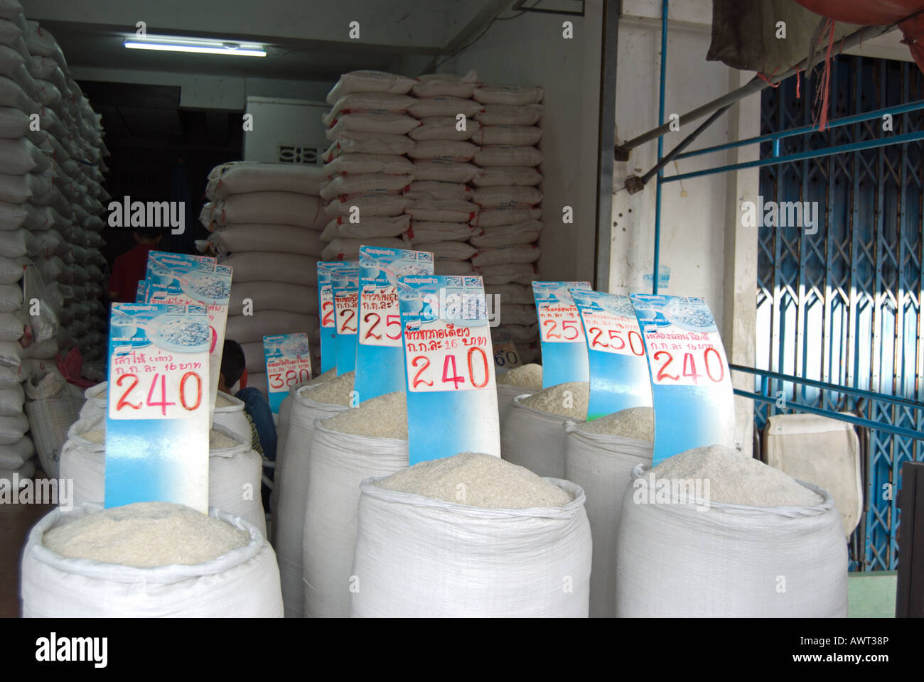 differently priced rice, graded according to quality, for sale from sacks at a market in phetchabun thailand - Stock Image