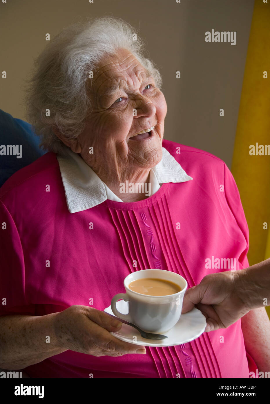 Happy senior old age pensioner elderly lady receives a cup of tea from carer companion - Stock Image
