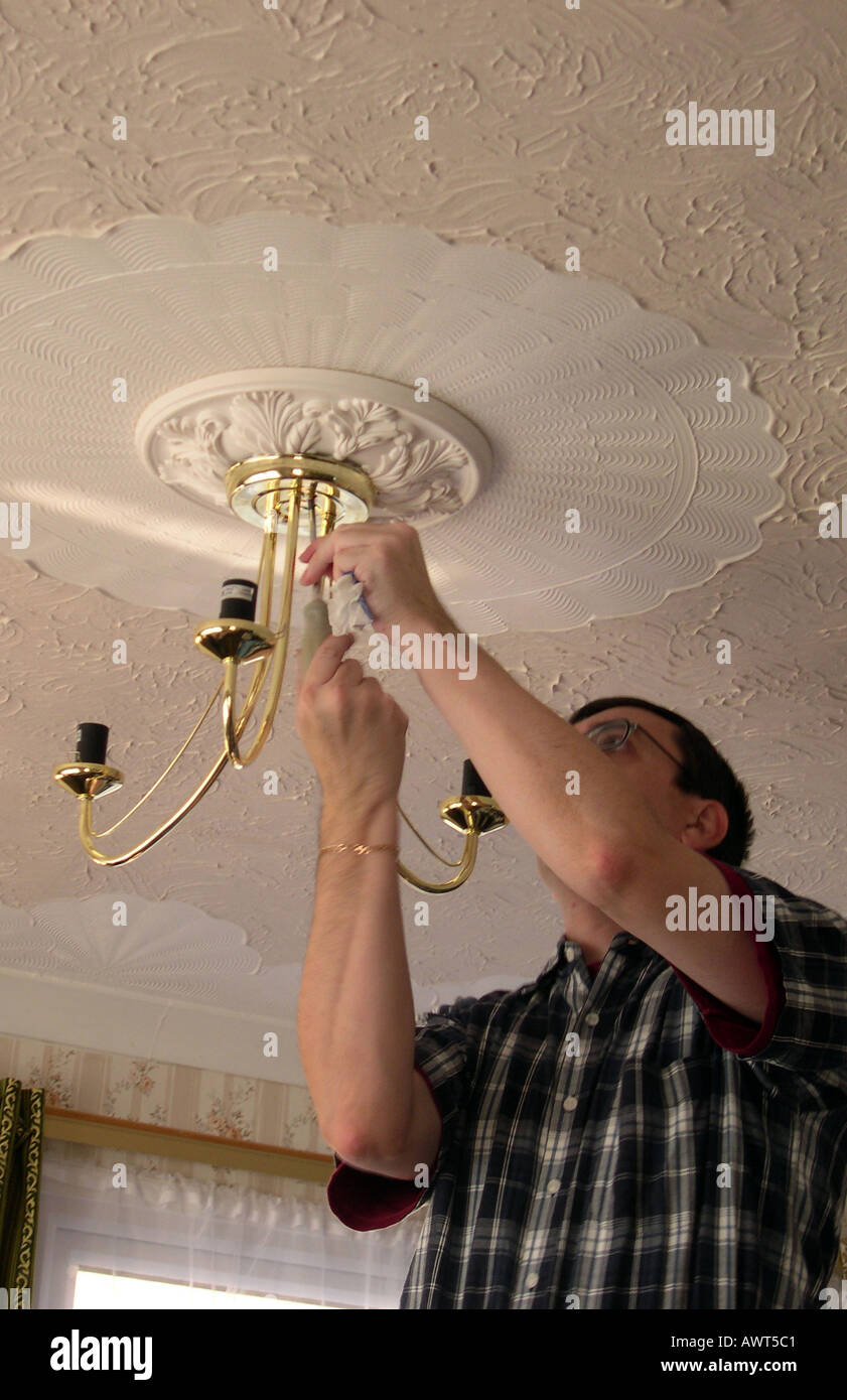 An Electrician Installing A Ceiling Light Fitting