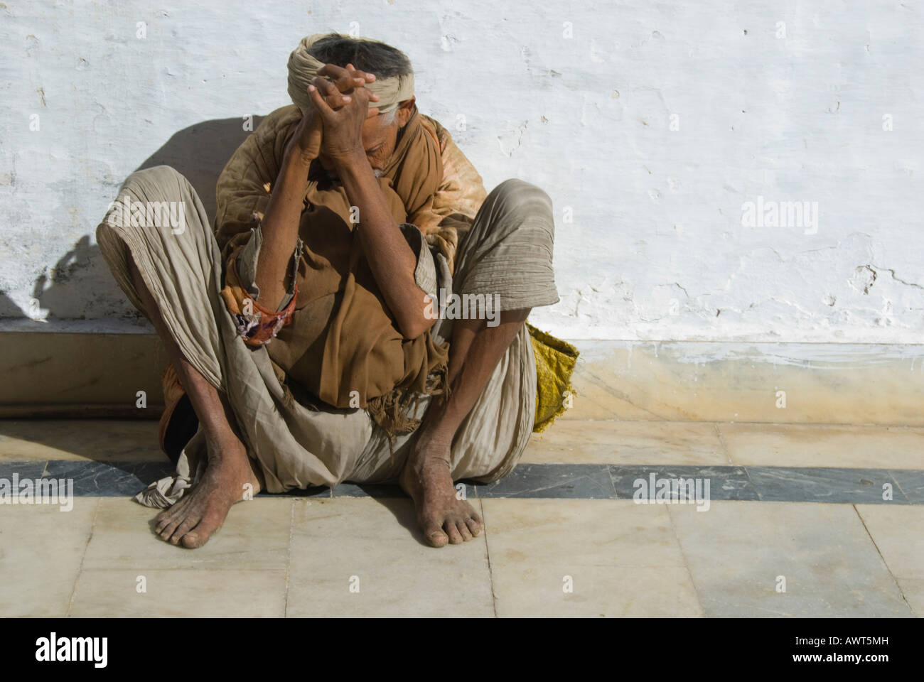 Portrait of an elderly man in a praying posture within a temple complex in Udaipur, Rajasthan, India. - Stock Image