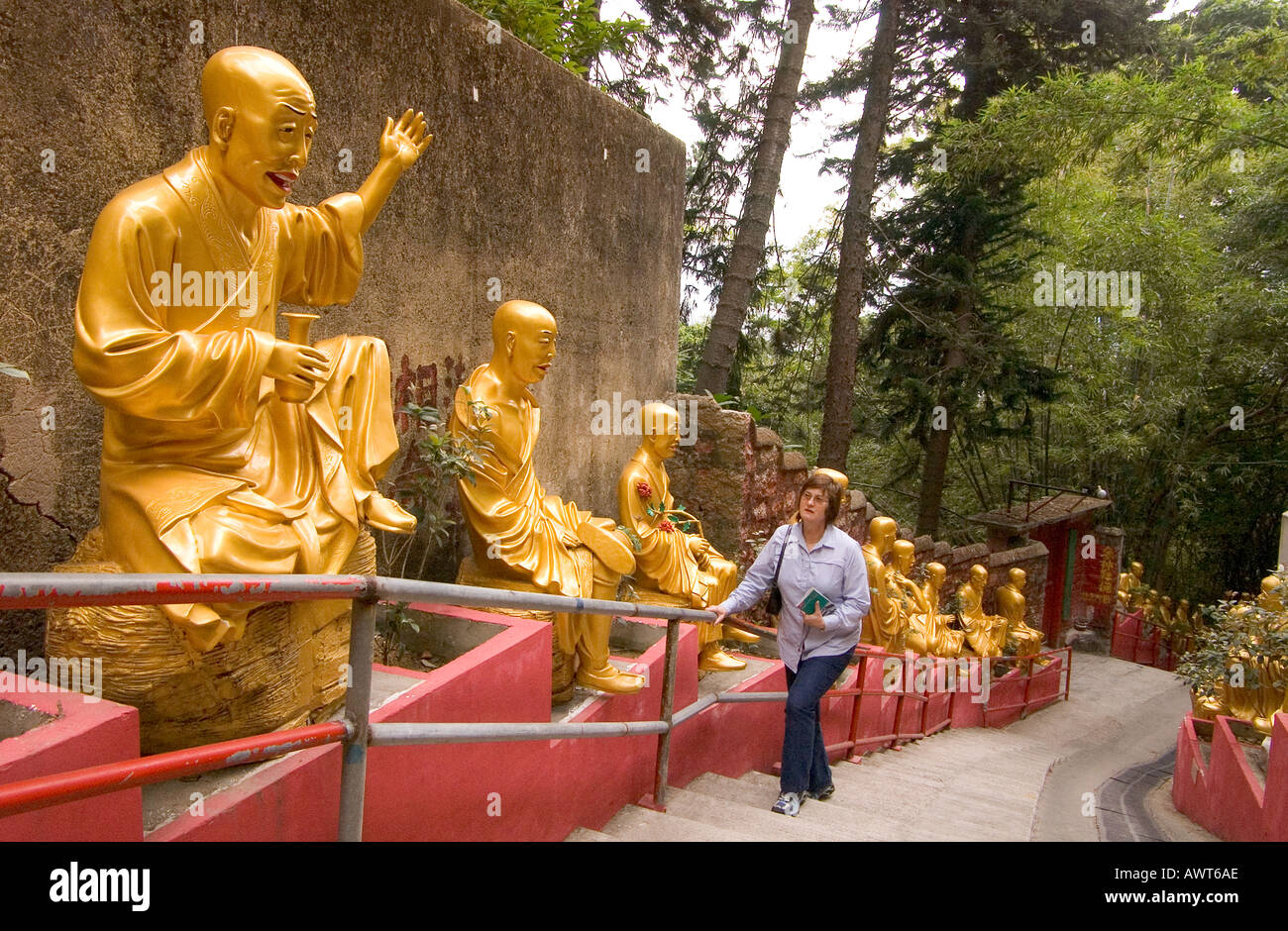 dh Ten Thousand Buddhas Monastery SHATIN HONG KONG Woman tourist walking up steps Golden Buddha statues 10000 temple Stock Photo