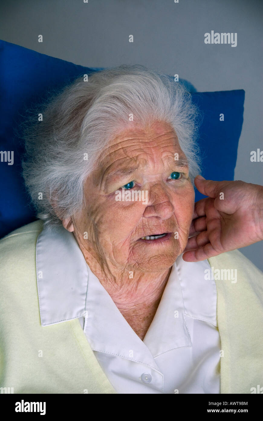 Apprehensive elderly woman with comforting hand of carer touching her face - Stock Image