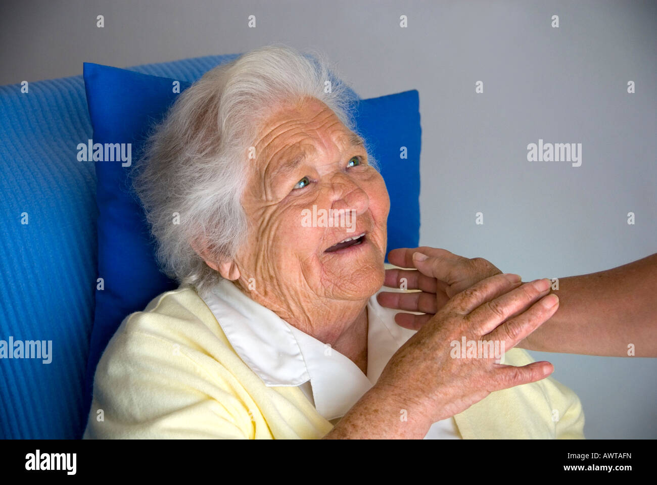 Contented smiling elderly woman looks up and touches comforting hand of carer Stock Photo