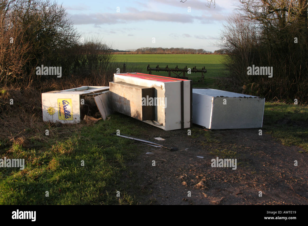 Discarded freezers by field entrance - Stock Image