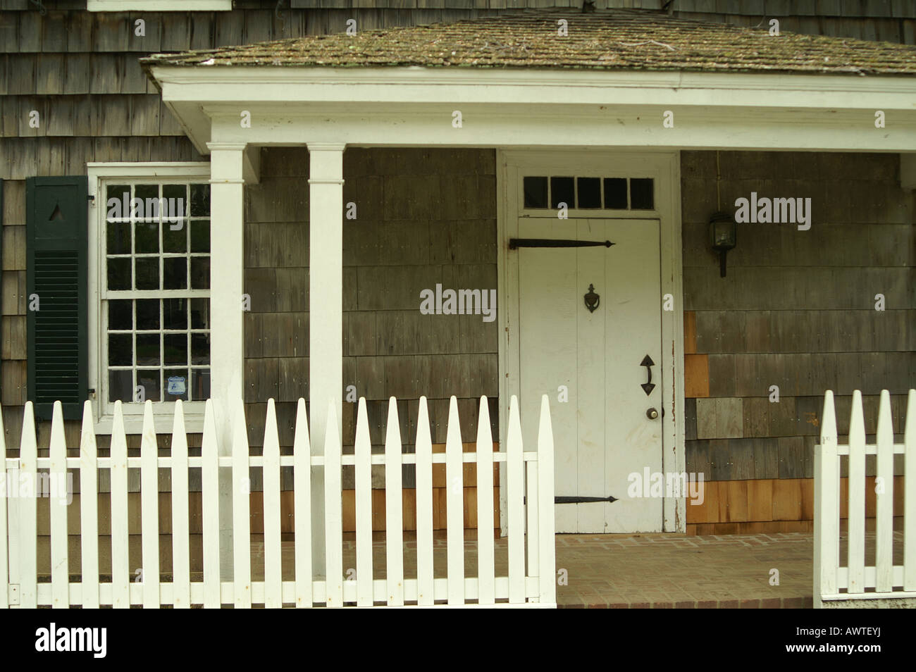 Colonial American House, With White Picket Fence And Strap Hinges On The  Door.