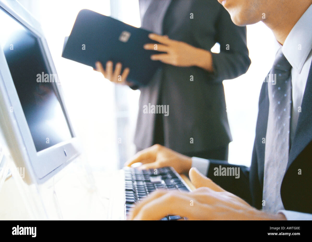 Businesswoman standing near businessman using computer, partial view - Stock Image