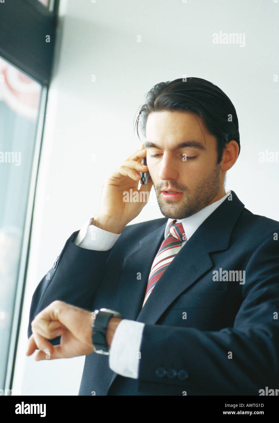 Businessman talking on cell phone, looking at watch - Stock Image