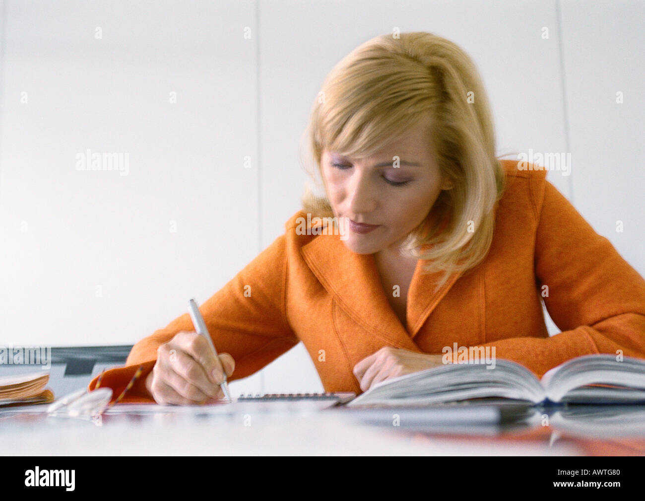 Businesswoman working at desk. - Stock Image