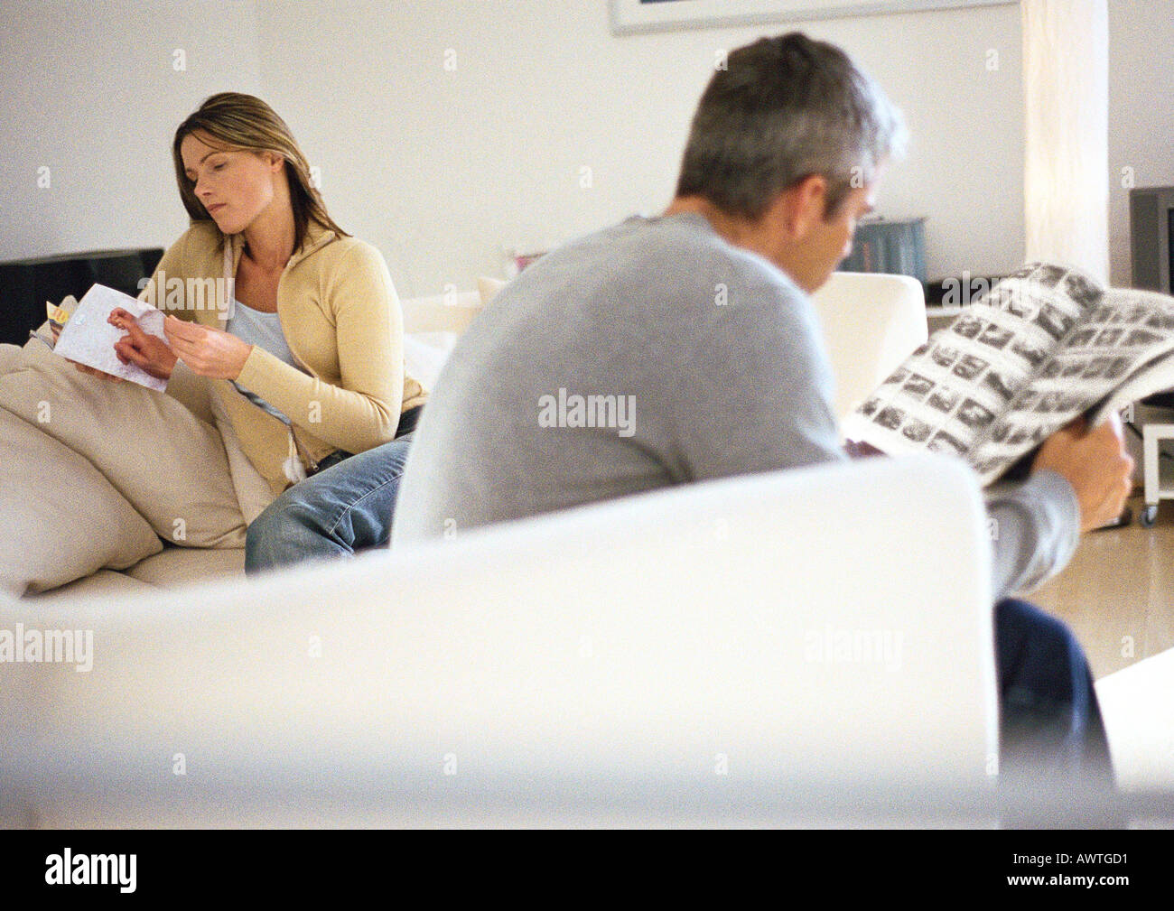 Man and woman sitting on couch reading Stock Photo