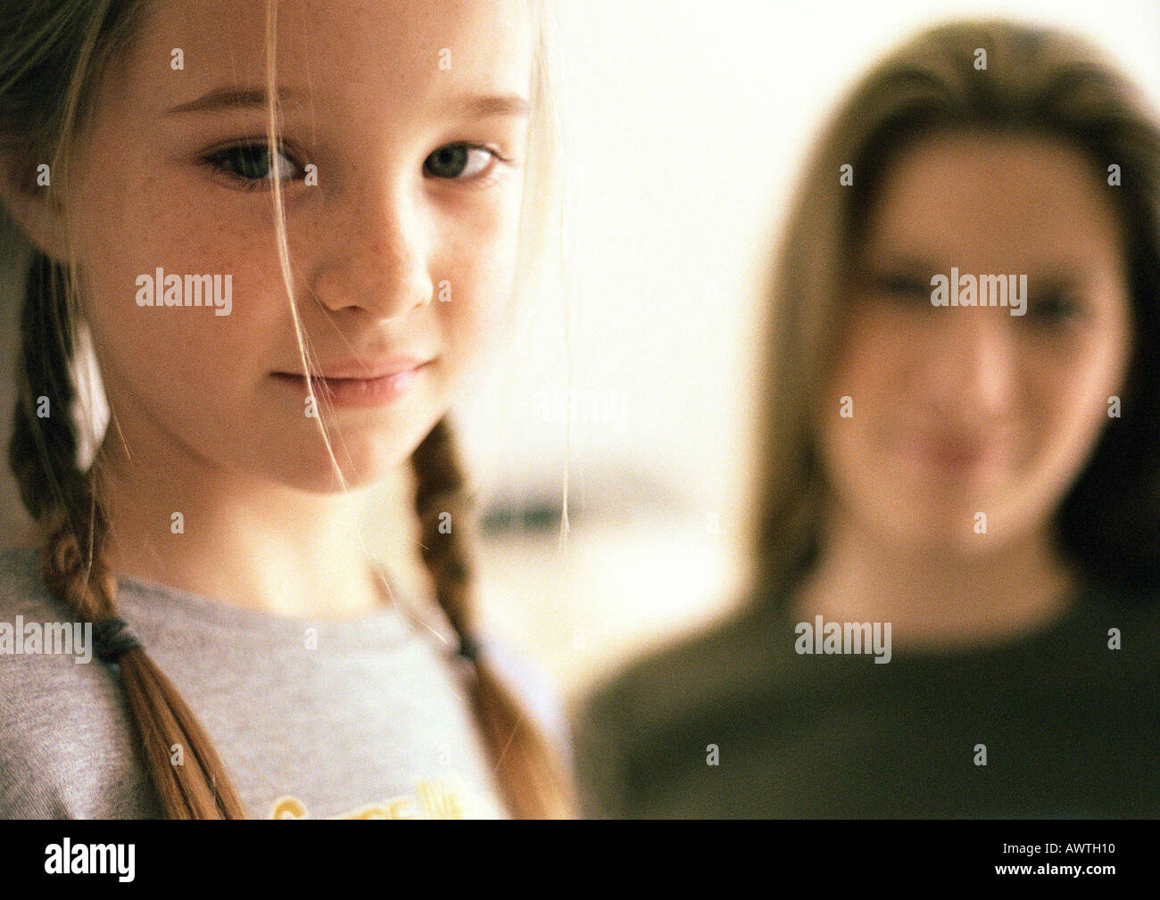 Two girls, younger girl in foreground, older girl blurred in background, portrait - Stock Image