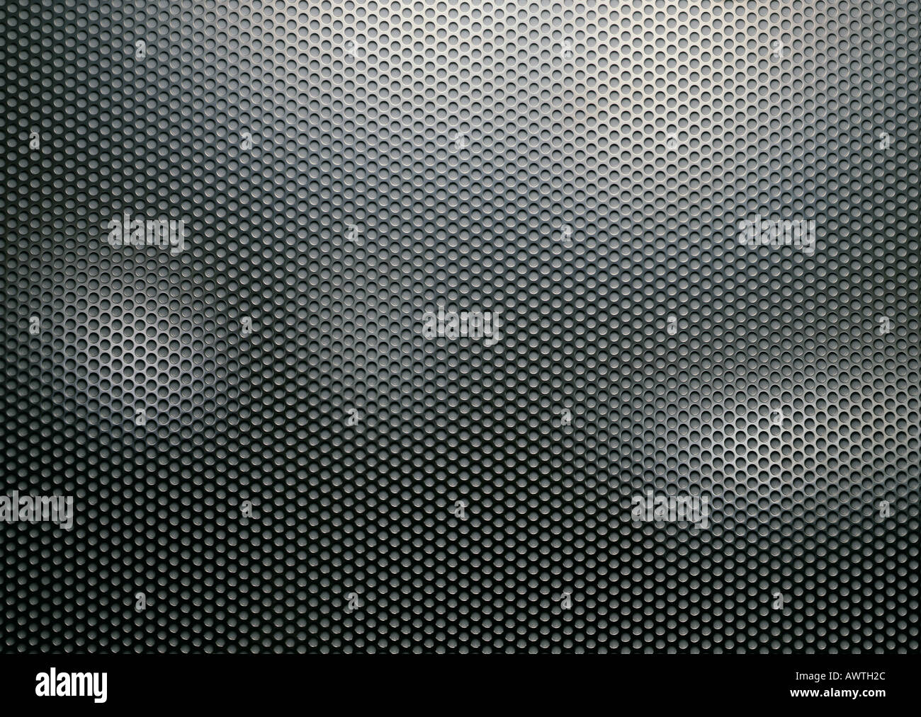 Metal sheet perforated with holes, close-up, full frame - Stock Image
