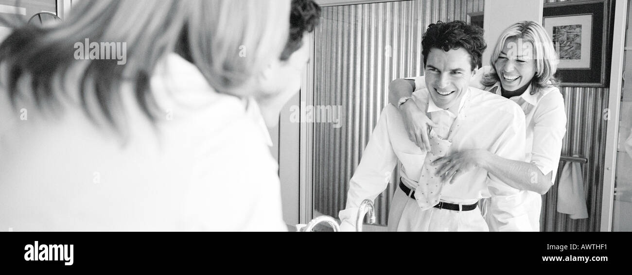 Woman standing behind man tying man's tie, laughing, b&w, panoramic view - Stock Image