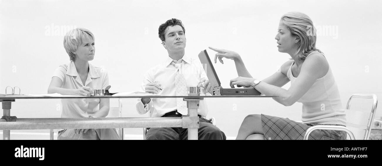 Three people sitting at table, one talking and pointing to laptop screen, b&w, panoramic view - Stock Image