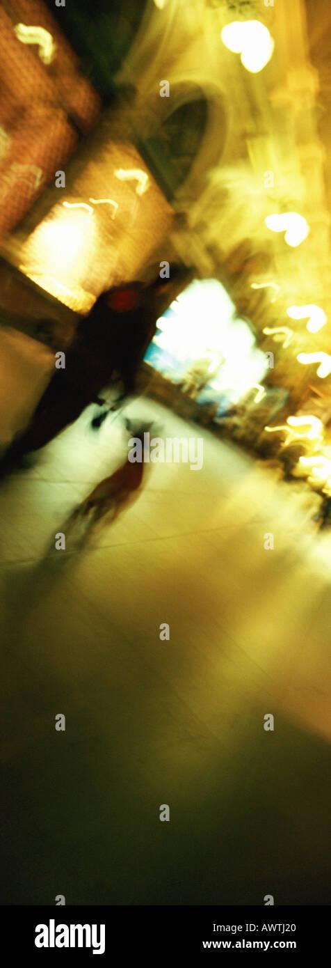 Man walking dog at night, blurred - Stock Image