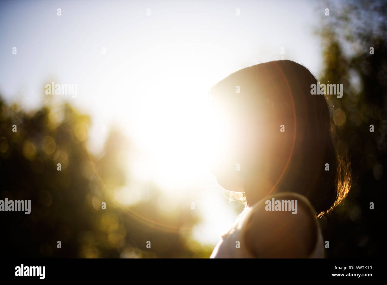 Girl backlit by evening sun - Stock Image
