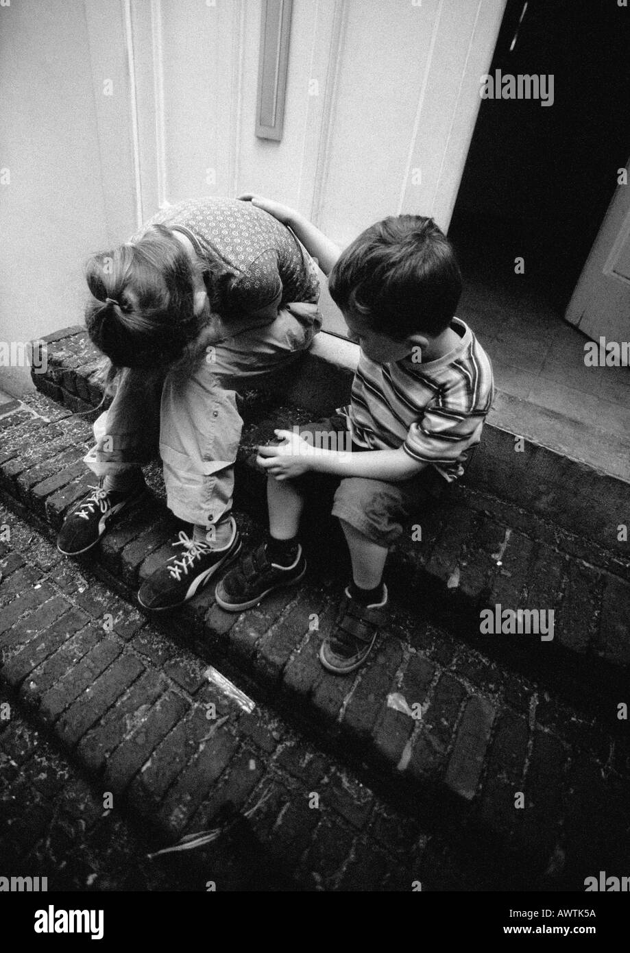 Two children on stairs, one holding head in hands, b&w - Stock Image