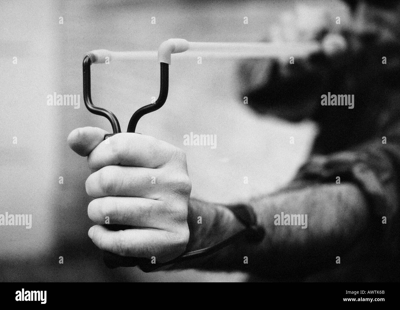Hands holding sling shot, close-up, b&w - Stock Image