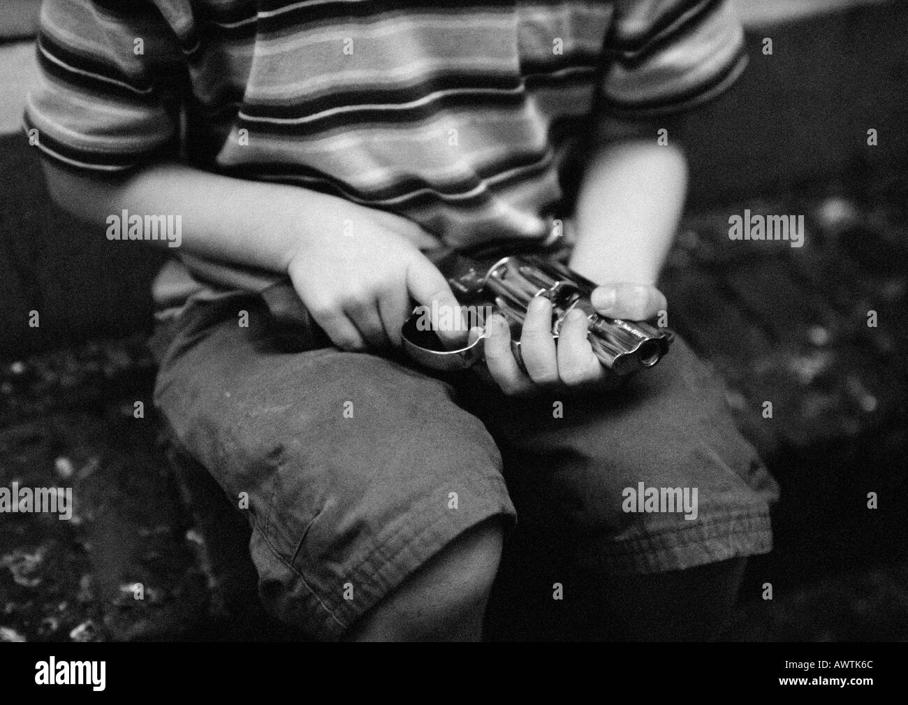 Child holding gun, mid-section, b&w - Stock Image