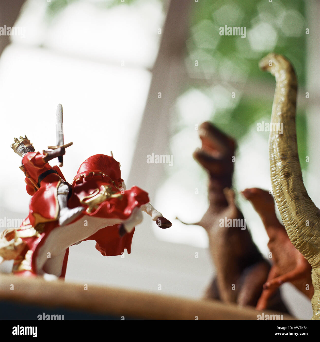 Toy knight fighting against toy dinosaurs - Stock Image