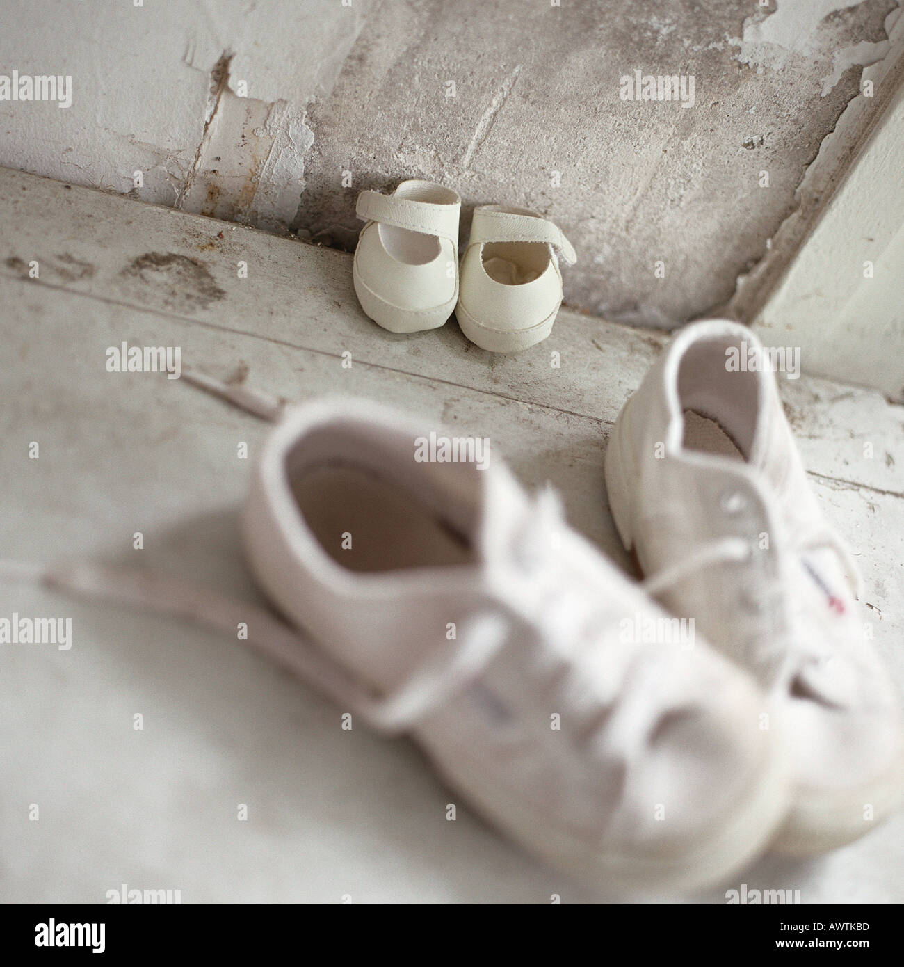 Two pairs of children's shoes on floor - Stock Image
