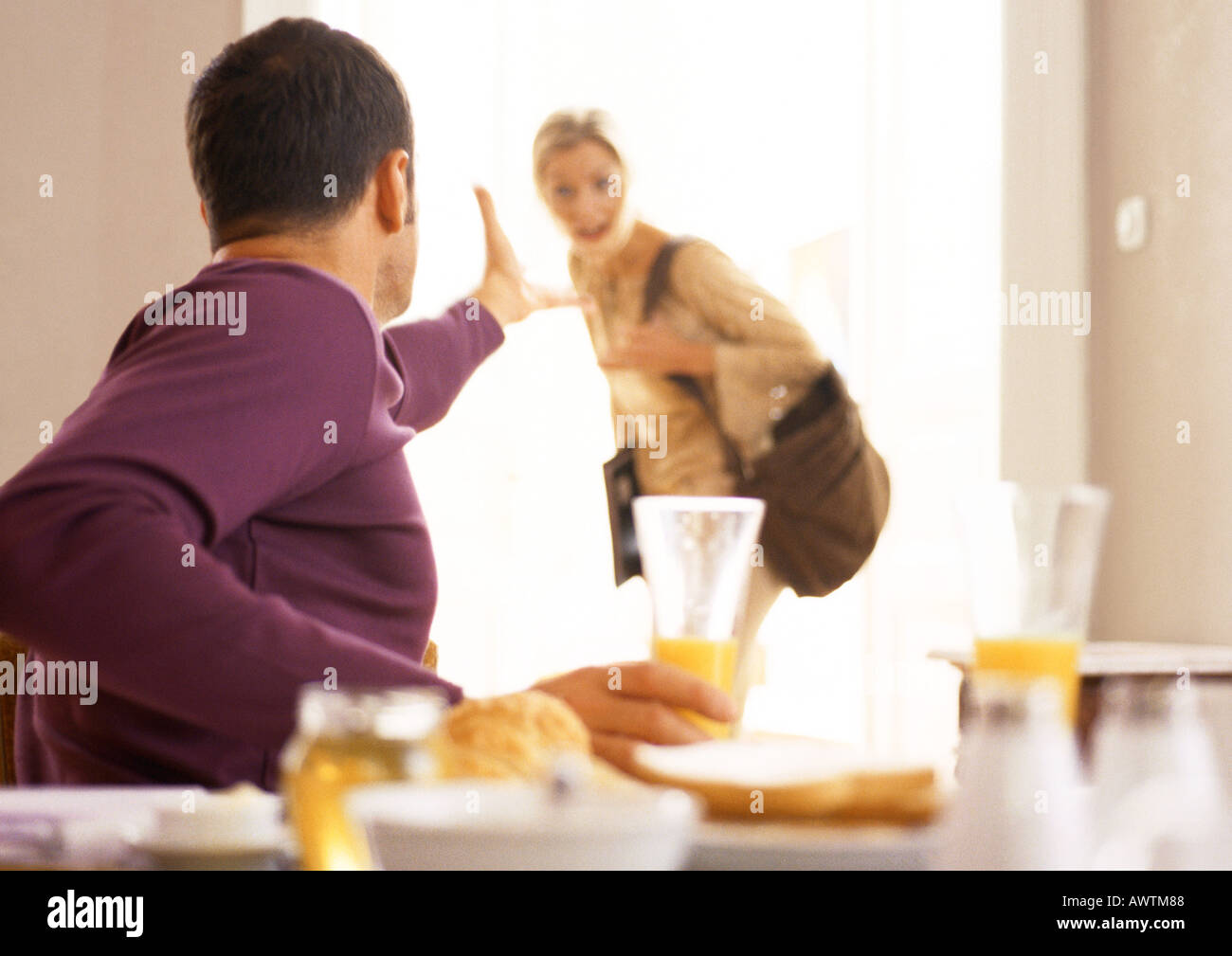 Man gesturing to woman leaving. - Stock Image