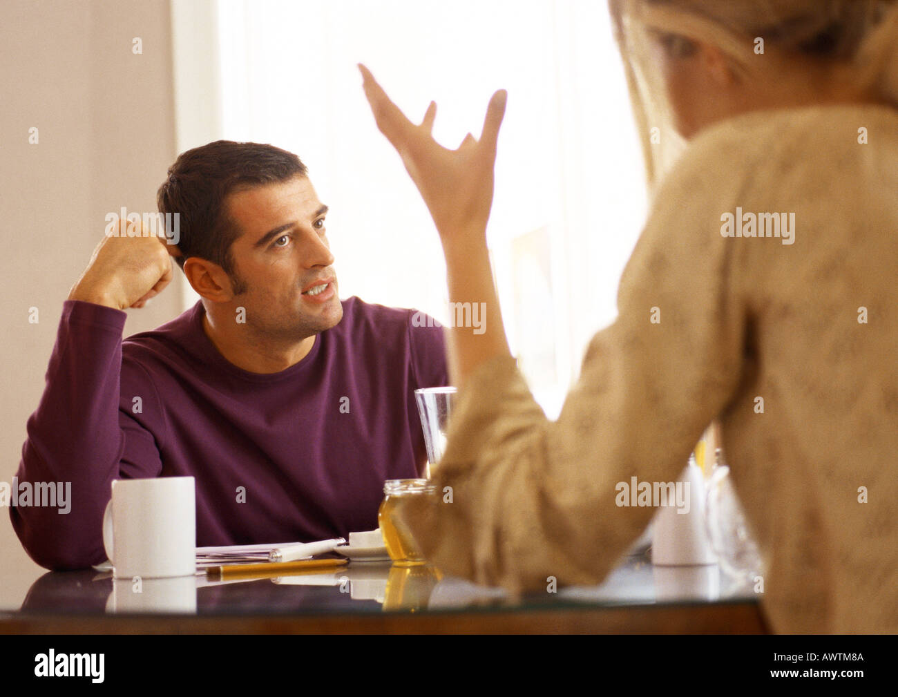 Woman sitting across from man at table, rear view. - Stock Image