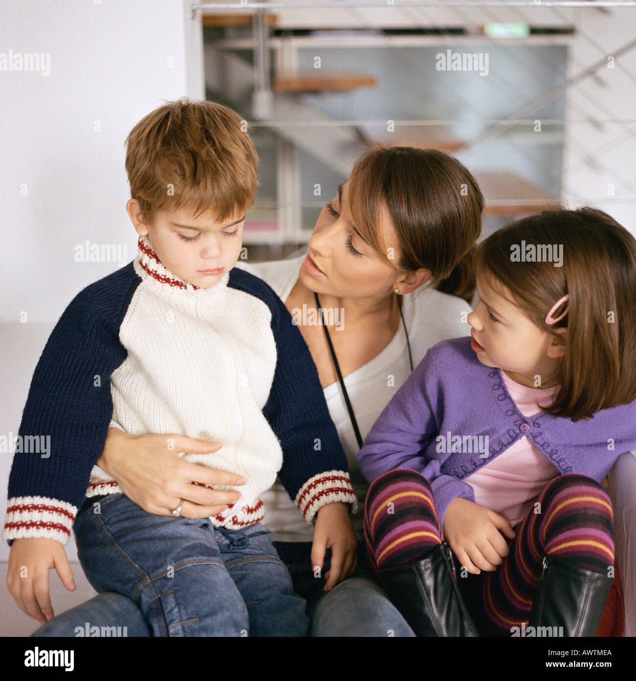 Mother sitting with children, looking at son - Stock Image