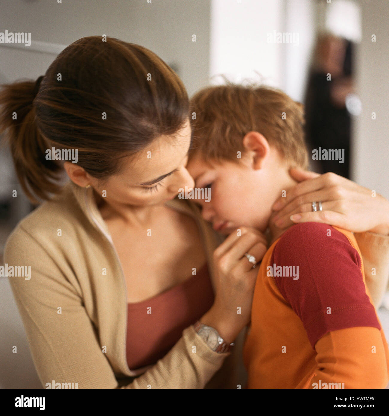 Woman with little boy's head on her shoulder - Stock Image